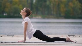 Flickan gör sporten nära sjön arkivfilmer
