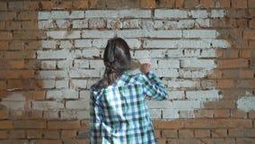 Flickan gör vit tegelstenväggen Hipsterflickabortförklaring väggarna hemma Håll i händerna av en borste med målarfärg lager videofilmer