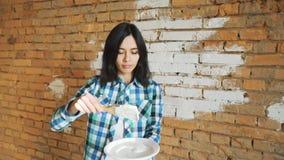 Flickan gör vit tegelstenväggen Hipsterflickabortförklaring väggarna hemma Håll i händerna av en borste med målarfärg arkivfilmer