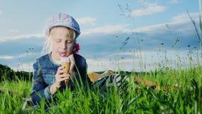 Flickan 5 gamla år äter glass på grön äng arkivfilmer