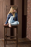 Flickan 6 gamla år i jeans och en blå skjorta sitter på hög stol Royaltyfri Bild