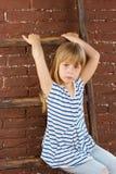 Flickan 6 gamla år i jeans och väst sitter på en stege nära tegelstenväggen arkivbilder