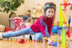 Flickan 8 gamla år spelas i rummet med leksaker arkivfoton