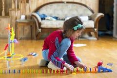 Flickan 8 gamla år spelas i rummet med leksaker fotografering för bildbyråer