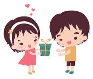 Flickan ger en gåva till hennes pojkvän Royaltyfri Fotografi