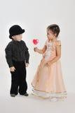 Flickan ger pojken hjärta-formad klubba Arkivfoto
