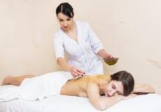 Flickan ges en terapeutisk massage med bihonung Arkivfoton