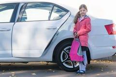 Flickan gick på en tur med bilen till en bildande institution-skola, med en portfölj i hennes händer royaltyfria foton
