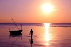 Flickan gick på stranden med en fiskebåt och en solnedgång Arkivfoto