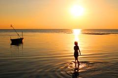 Flickan gick på stranden med en fiskebåt och en solnedgång Arkivbilder