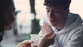 Flickan glatt och matar playfully hennes le pojkvän med pudding och därefter torkar försiktigt hans mun lager videofilmer