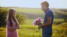 Flickan grälar med grabben, slår honom med blommor arkivfilmer
