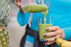 Flickan häller hennes favorit- gröna smoothie från blandaren till exponeringsglas royaltyfri foto