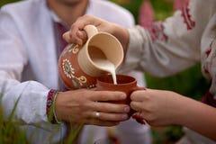 Flickan häller mjölkar från en tillbringare in i koppen för man royaltyfri fotografi