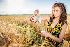 Flickan häller mjölkar in i ett exponeringsglas royaltyfria foton