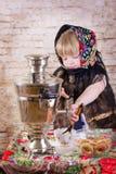 Flickan häller te från en samovar arkivfoto