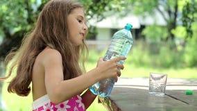 Flickan häller vatten från en flaska in i ett exponeringsglas arkivfilmer