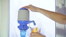 Flickan häller vatten in i exponeringsglas 4K lager videofilmer