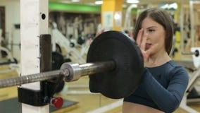Flickan hänger en tung hantel på skivstången för styrkautbildning, närbild lager videofilmer