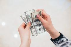 Flickan håller händerna i dollar arkivbild