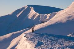Flickan håller hennes snowboard överst av henne i bergen i vinter Royaltyfri Bild