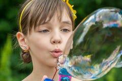 Flickan har blåst upp en stor och färgrik bubbla Royaltyfri Bild