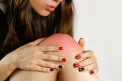 Flickan har en smärta i hans ben Rymma hans händer bak hans ben Arkivbild