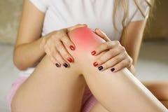 Flickan har en smärta i hans ben Rymma hans händer bak hans ben Royaltyfria Foton