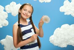 Flickan har en stor maskros i hennes händer, den iklädda randiga klänningen som poserar på en blå bakgrund med bomullsmoln, begre arkivfoto