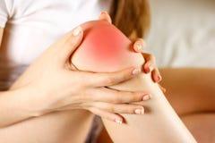 Flickan har ett öm knä Dåligt ben Fokusen av smärtar är markerat I royaltyfri fotografi