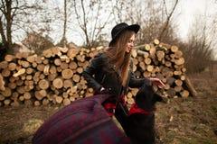 Flickan har gyckel med hennes hund mot bakgrunden av vedträt royaltyfria bilder