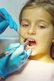 Flickan har hennes tänder att undersökas av tandläkaren Arkivbild