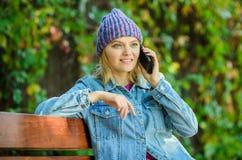 Flickan har mobiltelefonkonversation parkerar in koppla av på bänk, i srpring Väntande på pojkvän Dela lycklig nyheterna med arkivfoto