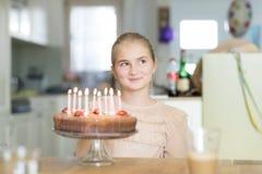 Flickan har roligt framme av en födelsedagkaka Royaltyfria Foton
