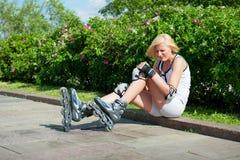 flickan har slågit att åka skridskor för knärullskateboradåkare arkivfoto