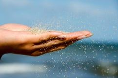 Flickan har vit sand i handen p? den h?rliga paradisstranden royaltyfria foton