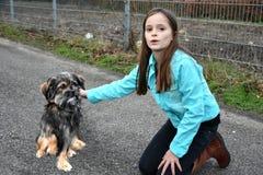 Flickan hjälper den lilla hunden royaltyfri bild