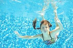 Flickan hoppar, dyker och simmar i den undervattens- pölen, det lyckliga aktiva barnet har gyckel under vatten, ungesport royaltyfri bild