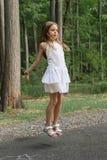 Flickan hoppar med hopprepet Arkivbild