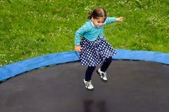Flickan hoppar på trampolinen Royaltyfria Bilder