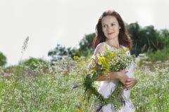 Flickan i ängen med en krans av fält-blommor Arkivfoto