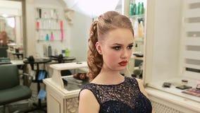 Flickan i aftonmodeklänning under makeup och frisyr ser i spegeln arkivfilmer