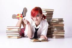 Flickan i animestil med godisen och böcker Royaltyfri Bild