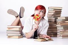 Flickan i animestil med godisen och böcker royaltyfri foto