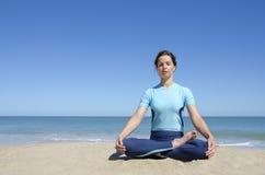 Flickan i arg-lagd benen på ryggen yogalotusblomma poserar på stranden Arkivfoto