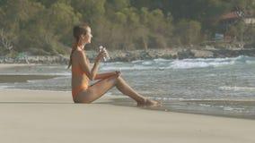 Flickan i baddräkt sitter och drinkvatten på havslinje stock video