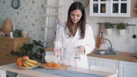 Flickan i badrock häller rent vatten in i exponeringsglas på kök, dricker det, ultrarapid stock video