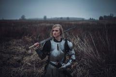 Flickan i bild av den Jeanne D `-bågen i harnesk och med svärdet i hennes händer står på äng closeup royaltyfri fotografi
