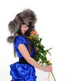 Flickan i blått klär med den framlade buketten av blommor Royaltyfri Foto