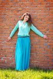 Flickan i blått klär på bakgrund för tegelstenvägg Arkivfoto